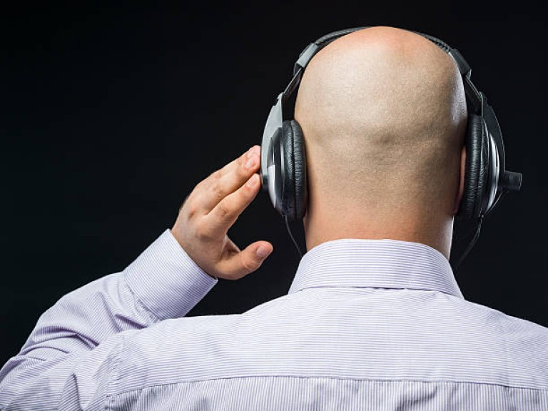 Bald man with headphones listening in dark on black background.